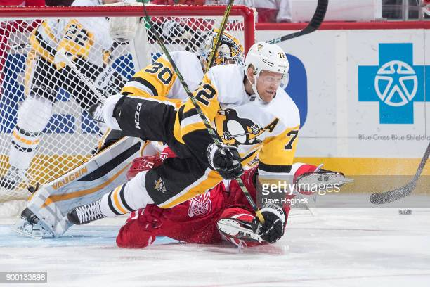Patric Hornqvist of the Pittsburgh Penguins battles with Dylan Larkin of the Detroit Red Wings in front of goaltender Matt Murray of the Penguins...