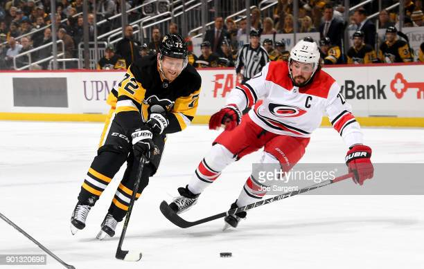 Patric Hornqvist of the Pittsburgh Penguins handles the puck against Justin Faulk of the Carolina Hurricanes at PPG Paints Arena on January 4 2018 in...