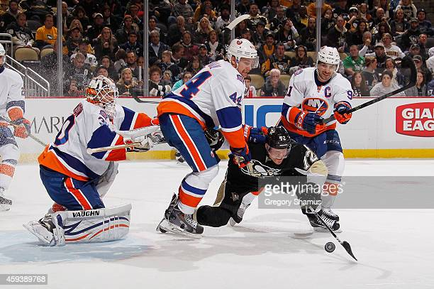 Patric Hornqvist of the Pittsburgh Penguins is knocked down while battling for the puck by Calvin de Haan and John Tavares of the New York Islanders...