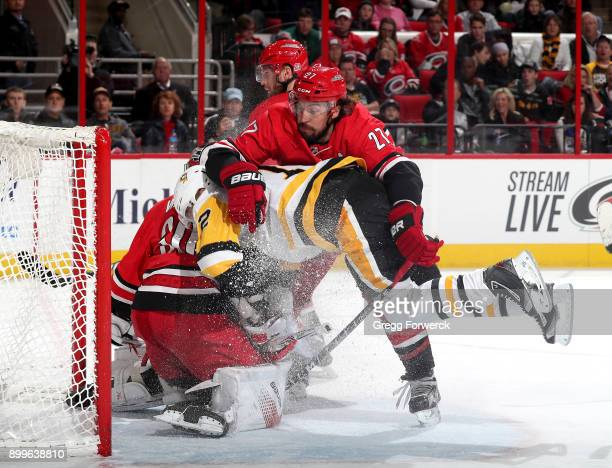 Patric Hornqvist of the Pittsburgh Penguins leaves his feet and drives into Cam Ward of the Carolina Hurricanes as Justin Faulk attempts to defend...