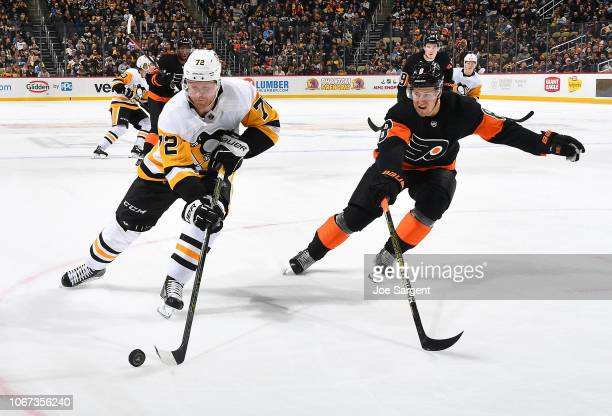Patric Hornqvist of the Pittsburgh Penguins moves the puck in front of Robert Hagg of the Philadelphia Flyers at PPG Paints Arena on December 1 2018...