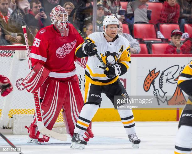 Patric Hornqvist of the Pittsburgh Penguins sets up in front of Jimmy Howard of the Detroit Red Wings during an NHL game at Little Caesars Arena on...