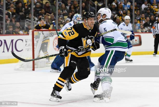 Patric Hornqvist of the Pittsburgh Penguins throws a check into Derrick Pouliot of the Vancouver Canucks in the second period during the game at PPG...