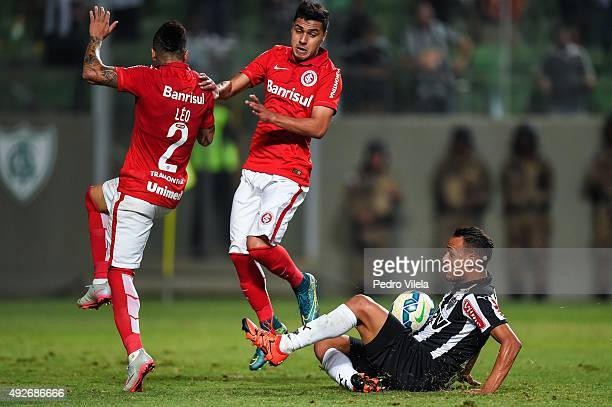 Patric of Atletico MG and Leo and Alisson Farias of Internacional battle for the ball during a match between Atletico MG and Internacional as part of...