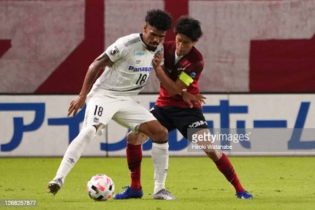 Patric of Gamba Osaka and Atsuto Uchida of Kashima Antlers compete for the ball during the J.League Meiji Yasuda J1 match between Kashima Antlers and...