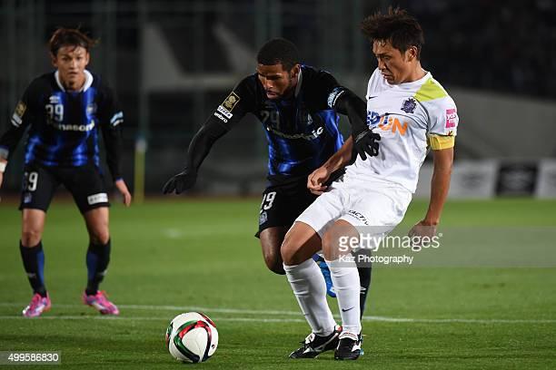 Patric of Gamba Osaka and Toshihiro Aoyama of Sanfrecce Hiroshima compete for the ball during the J.League 2015 Championship final 1st leg match...