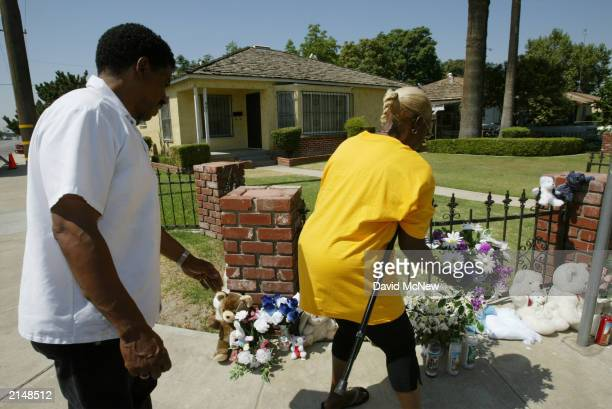 Patrica Quinney brings flowers to a makeshift memorial at the house of a family of five found murdered July 9 2003 in Bakersfield California...