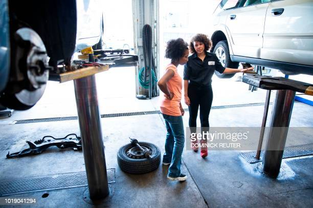 Patrice Banks founder and owner of the Girls Auto Clinic discusses vehicle lift safety with a crew member at her garage in Upper Darby Pennsylvania...