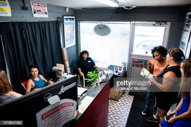 Patrice Banks founder and owner of the Girls Auto Clinic joins her staff on a break in the reception area of her garage in Upper Darby Pennsylvania...