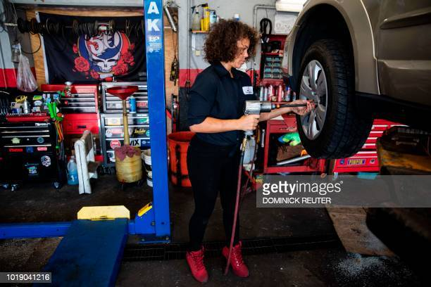 Patrice Banks founder and owner of the Girls Auto Clinic mounts a wheel on a car at her garage in Upper Darby Pennsylvania on August 7 2018 On the...