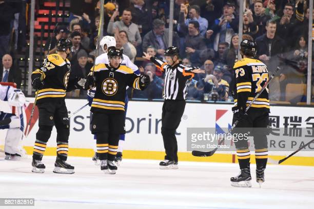 Patrice Bergeorn, Brad Marchand and Charlie McAvoy of the Boston Bruins celebrate a goal in the first period against the Tampa Bay Lightning at the...