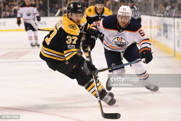 Patrice Bergeorn of the Boston Bruins fights for the puck against Mark Letestu of the Edmonton Oilers at the TD Garden on November 26 2017 in Boston...