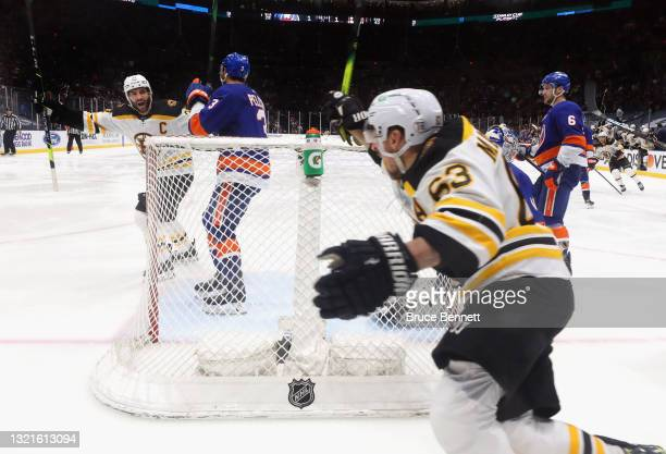 Patrice Bergeron and Brad Marchand of the Boston Bruins celebrate their overtime victory over the New York Islanders in Game Three of the Second...