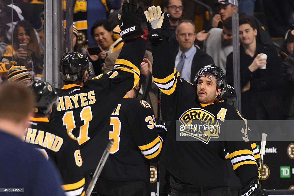 Patrice Bergeron #37 and Jimmy Hayes #11 of the Boston Bruins high five after a win against the Detroit Red Wings at the TD Garden on November 14, 2015 in Boston, Massachusetts.