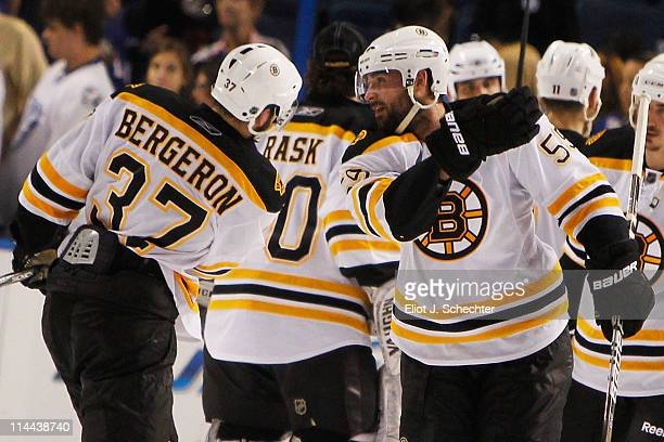 Patrice Bergeron and Johnny Boychuk of the Boston Bruins celebrate defeating the Tampa Bay Lightning 2 to 0 in Game Three of the Eastern Conference...