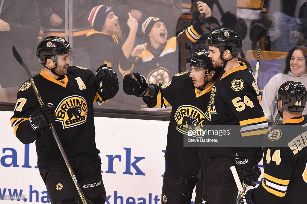 Patrice Bergeron #37, Brad Marchand #63 and Adam McQuaid #54 of the Boston Bruins celebrate a goal against the Los Angeles Kings at the TD Garden on January 31, 2015 in Boston, Massachusetts.