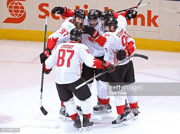 Patrice Bergeron of Team Canada is congratulated by his teammates after scoring a third period goal against Team Europe during Game Two of the World...