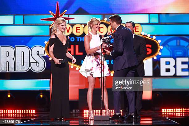 Patrice Bergeron of the Boston Bruins accepts the Frank Selke trophy onstage from Kathryn Tappen during the 2015 NHL Awards at MGM Grand Garden Arena...