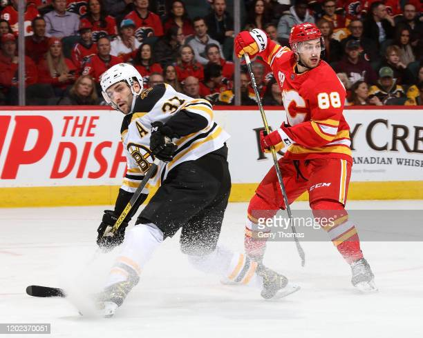 Patrice Bergeron of the Boston Bruins and Andrew Mangiapane of the Calgary Flames skate during an NHL game on February 21, 2020 at the Scotiabank...