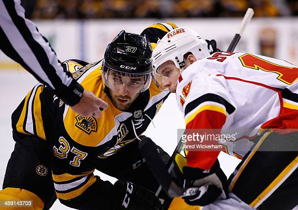 Patrice Bergeron of the Boston Bruins and Matt Stajan of the Calgary Flames faceoff during the game at TD Garden on December 17 2013 in Boston...