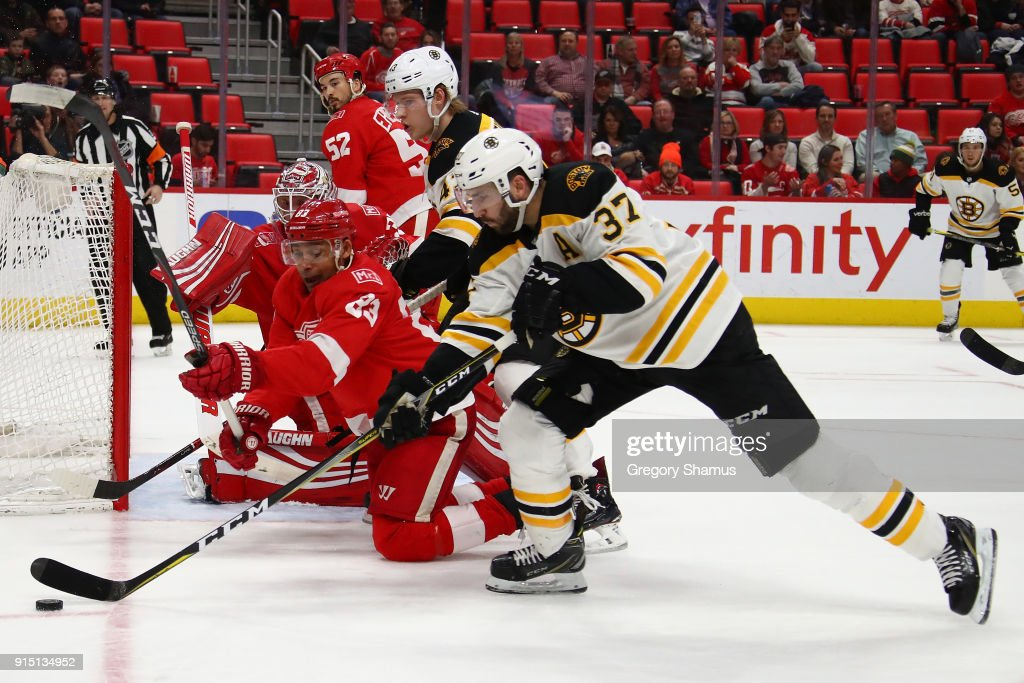 Patrice Bergeron #37 of the Boston Bruins battles for the puck with Trevor Daley #83 of the Detroit Red Wings during the third period at Little Caesars Arena on February 6, 2018 in Detroit, Michigan. Boston won the game 3-2.