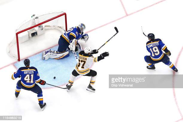 Patrice Bergeron of the Boston Bruins celebrates a first period goal by teammate Brad Marchand past Jordan Binnington of the St Louis Blues in Game...