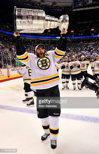 Patrice Bergeron of the Boston Bruins celebrates by hoisting the Stanley Cup after defeating the Vancouver Canucks 40 in Game Seven of the 2011 NHL...