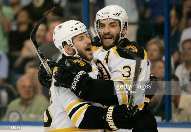 Patrice Bergeron of the Boston Bruins celebrates his first period goal against the Tampa Bay Lightning with Mark Recchi of the Boston Bruins in Game...