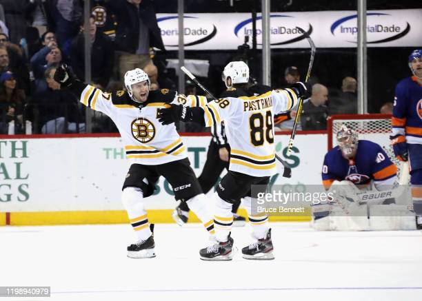 Patrice Bergeron of the Boston Bruins celebrates his game winning power-play goal at 2:33 of overtime against the New York Islanders and is joined by...