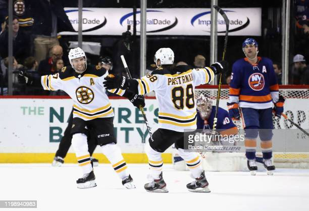 Patrice Bergeron of the Boston Bruins celebrates his game winning powerplay goal at 233 of overtime against the New York Islanders and is joined by...
