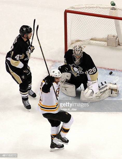 Patrice Bergeron of the Boston Bruins celebrates his gamewinning goal in overtime against Simon Despres and MarcAndre Fleury of the Pittsburgh...