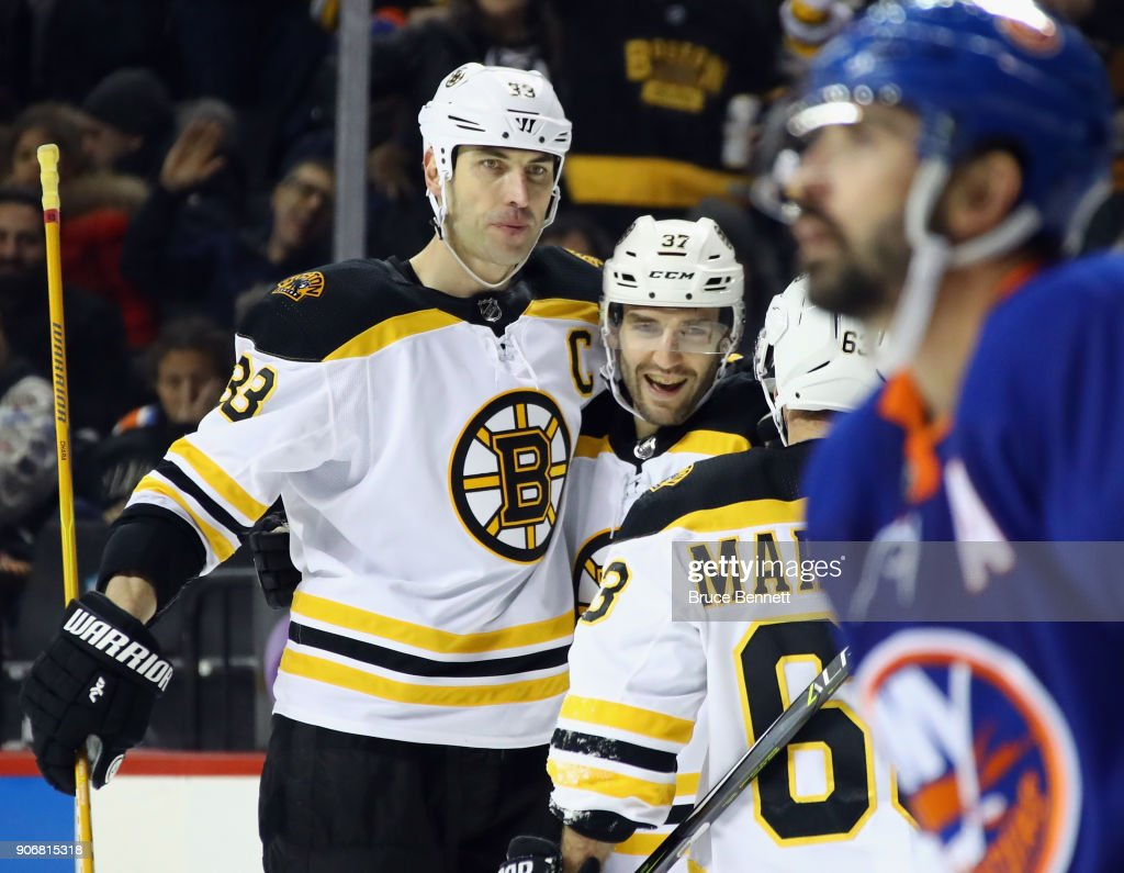 Patrice Bergeron #37 of the Boston Bruins (c) celebrates his hattrick at 3:45 of the third period against the New York Islanders and is joined by Zdeno Chara #33 (l) and Brad Marchand #63 (r) at the Barclays Center on January 18, 2018 in the Brooklyn borough of New York City.