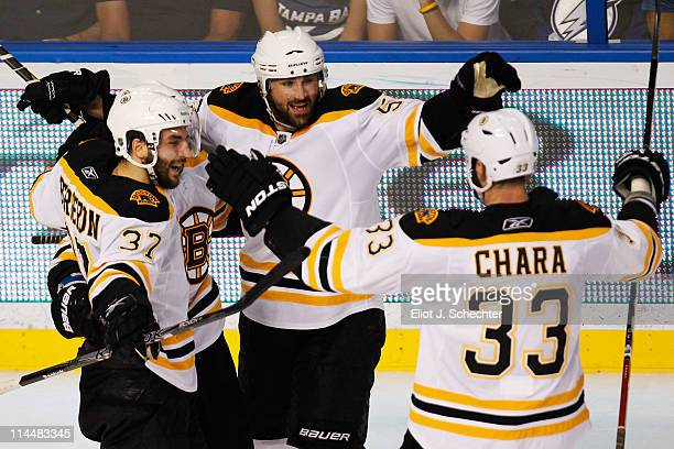 Patrice Bergeron of the Boston Bruins celebrates his second first period goal with teammates Zdeno Chara and Johnny Boychuk of the Boston Bruins in...