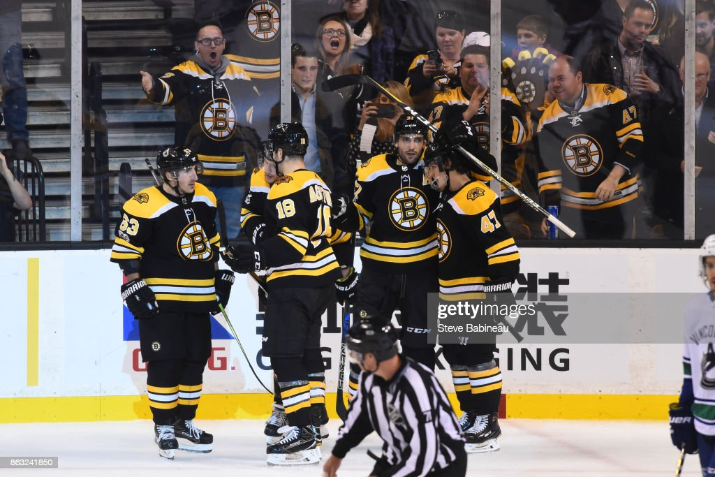 Patrice Bergeron #37 of the Boston Bruins celebrates his third period goal with his line mates against the Vancouver Canucks at the TD Garden on October 19, 2017 in Boston, Massachusetts.