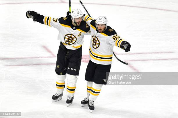 Patrice Bergeron of the Boston Bruins celebrates with Brad Marchand after scoring on Curtis McElhinney of the Carolina Hurricanes during the second...