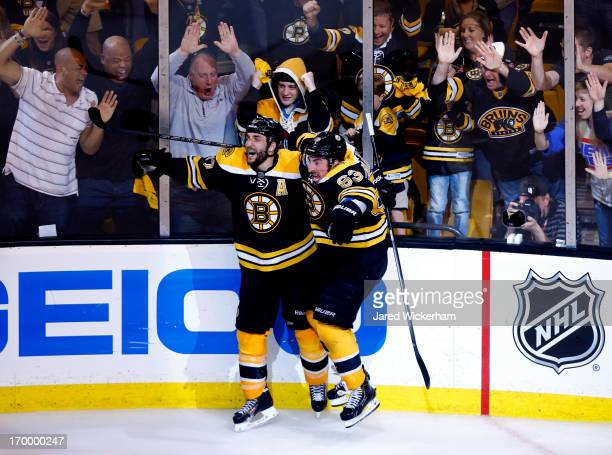 Patrice Bergeron of the Boston Bruins celebrates with Brad Marchand after scoring the game winning goal in overtime to beat the Pittsburgh Penguins...