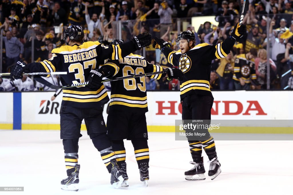 Patrice Bergeron #37 of the Boston Bruins celebrates with Brad Marchand #63 and David Pastrnak #88 after scoring a goal against the Tampa Bay Lightning during the first period Game Three of the Eastern Conference Second Round during the 2018 NHL Stanley Cup Playoffs at TD Garden on May 2, 2018 in Boston, Massachusetts.