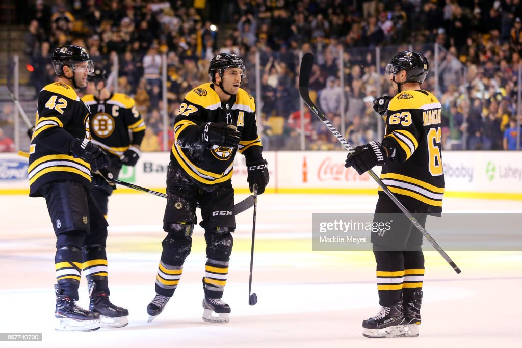 Patrice Bergeron #37 of the Boston Bruins celebrates with David Backes #42 and Brad Marchand #63 during the third period at TD Garden on December 23, 2017 in Boston, Massachusetts. The Bruins defeat the Red Wings 3-1.