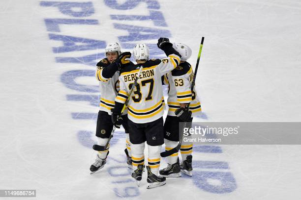 Patrice Bergeron of the Boston Bruins celebrates with David Pastrnak and Brad Marchand after scoring a goal on Curtis McElhinney of the Carolina...