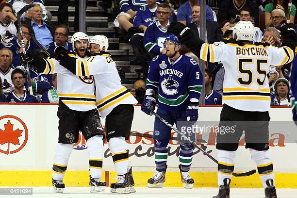 Patrice Bergeron of the Boston Bruins celebrates with Gregory Campbell and Johnny Boychuk after he scored the 3rd goal in the second period against...
