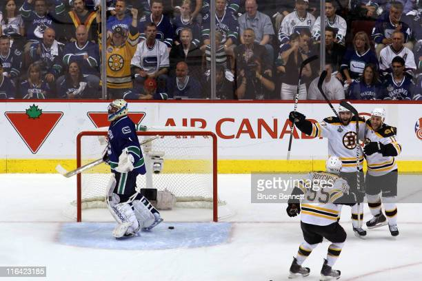 Patrice Bergeron of the Boston Bruins celebrates with Gregory Campbell and Johnny Boychuk after he scored the 3rd goal in the second period as...