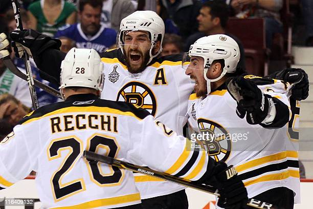 Patrice Bergeron of the Boston Bruins celebrates with his teammates Mark Recchi and Brad Marchand after scoring a goal in the first period against...