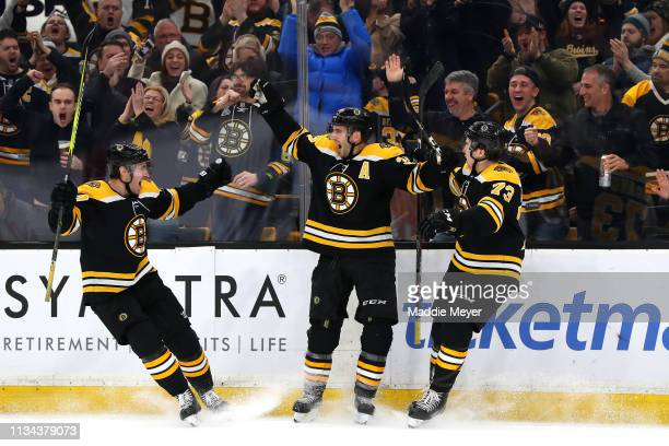 Patrice Bergeron of the Boston Bruins celebrates with John Moore and Charlie McAvoy after scoring a goal against the Florida Panthers during the...