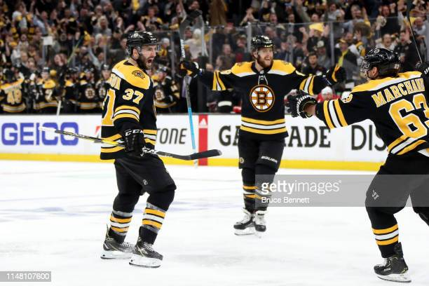Patrice Bergeron of the Boston Bruins celebrates with teammates after scoring a goal during the third period against the Carolina Hurricanes in Game...