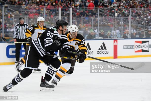 Patrice Bergeron of the Boston Bruins defends Carl Dahlstrom of the Chicago  Blackhawks during the 2019. 2019 Bridgestone NHL Winter Classic ... 0a0a421f8