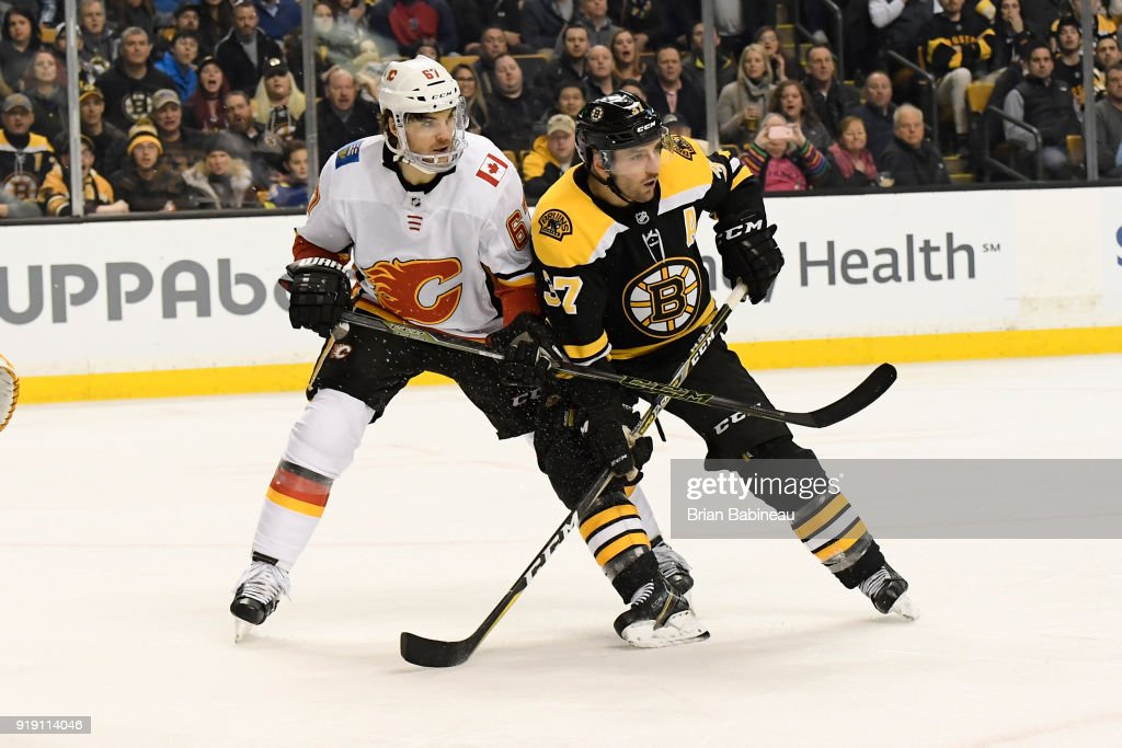 Patrice Bergeron #37 of the Boston Bruins fights for position against Michael Frolik #67 of the Calgary Flames at the TD Garden on February 13, 2018 in Boston, Massachusetts.