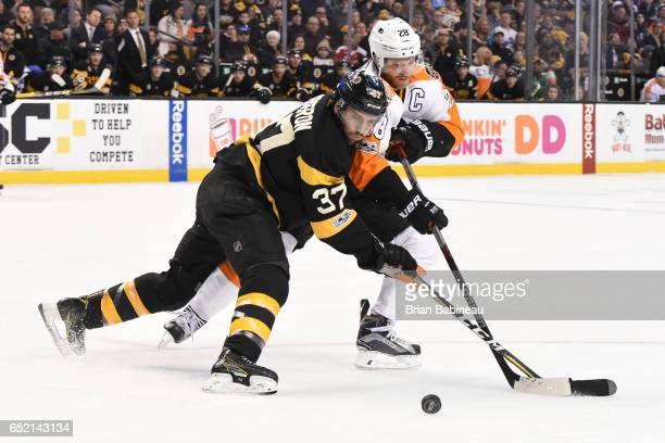 Patrice Bergeron of the Boston Bruins fights for the puck against Claude Giroux of the Philadelphia Flyers at the TD Garden on March 11 2017 in...