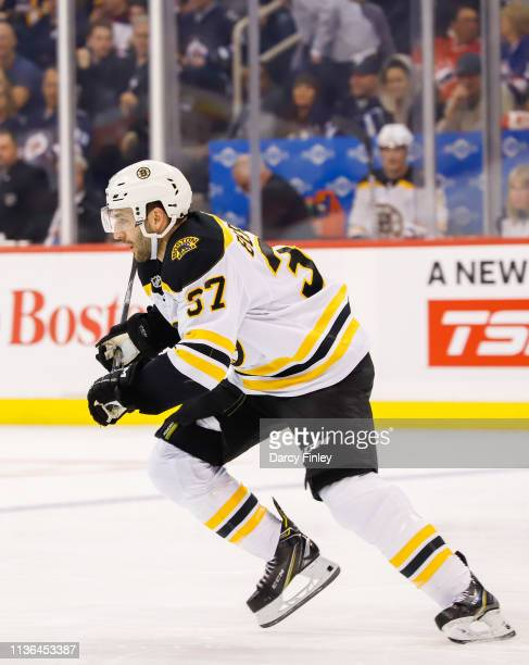 Patrice Bergeron of the Boston Bruins follows the play down the ice during first period action against the Winnipeg Jets at the Bell MTS Place on...