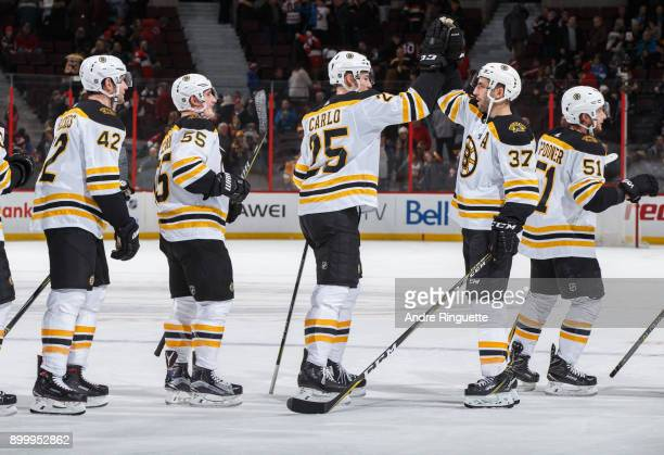 Patrice Bergeron of the Boston Bruins highfives Brandon Carlo after their win over the Ottawa Senators at Canadian Tire Centre on December 30 2017 in...