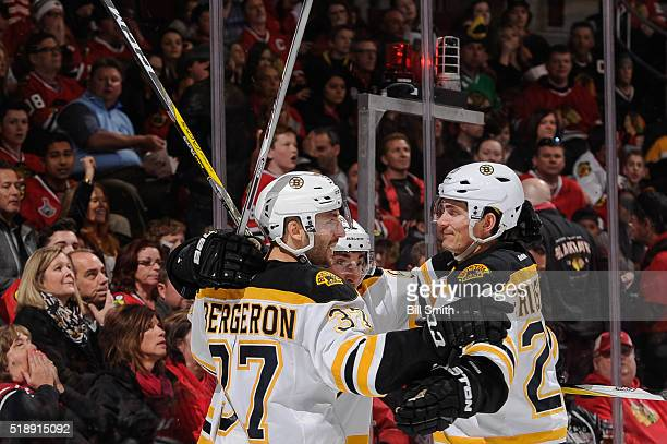Patrice Bergeron of the Boston Bruins hugs Loui Eriksson after scoring his second goal against the Chicago Blackhawks in the third period of the NHL...